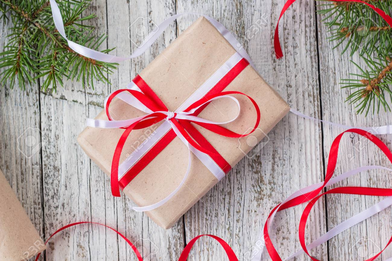 packing christmas presents in kraft paper with red and white stock