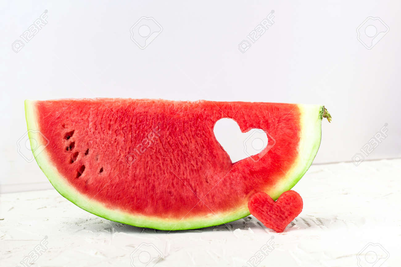 Fresh juicy watermelon slice with heart shape hole on white background. Valentines, love, summer concept with copy space - 138921196