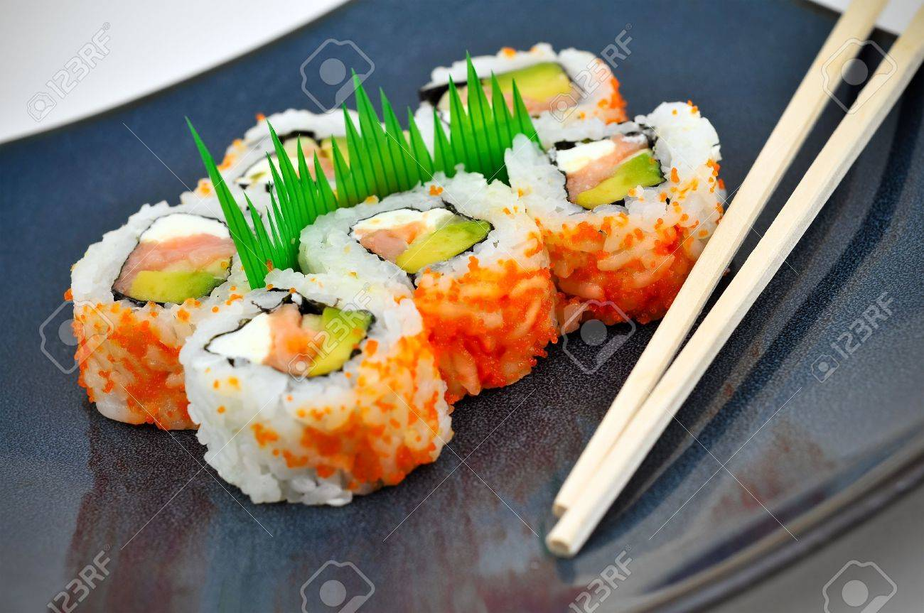 Sushi California or Philly rolls appetizer with rice, avocado, and salmon served on a blue dinner plate with chopsticks. Stock Photo - 3517090