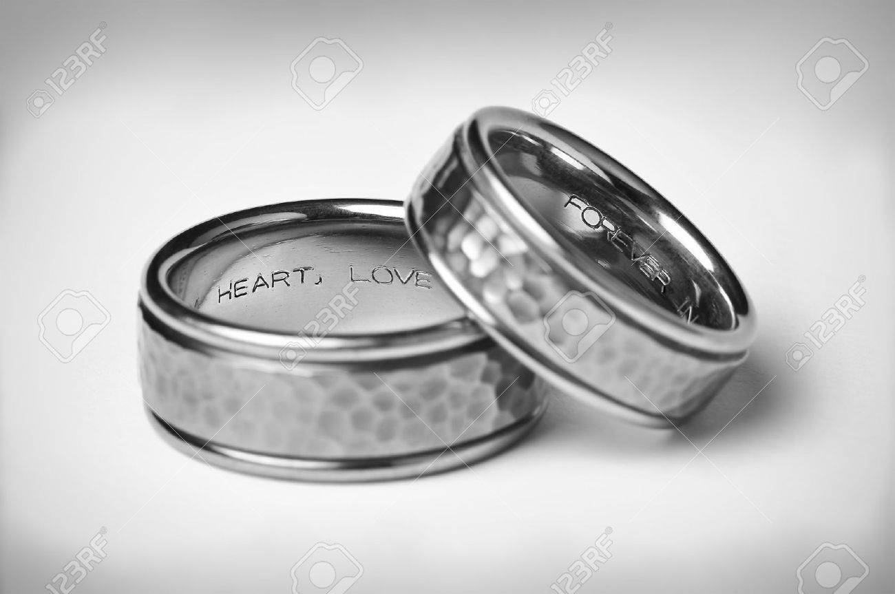 Two Titanium Silver Wedding Bands with heart, love, and forever inscriptions on a soft white gradient background with vignette symbolizing marriage. Stock Photo - 3654042