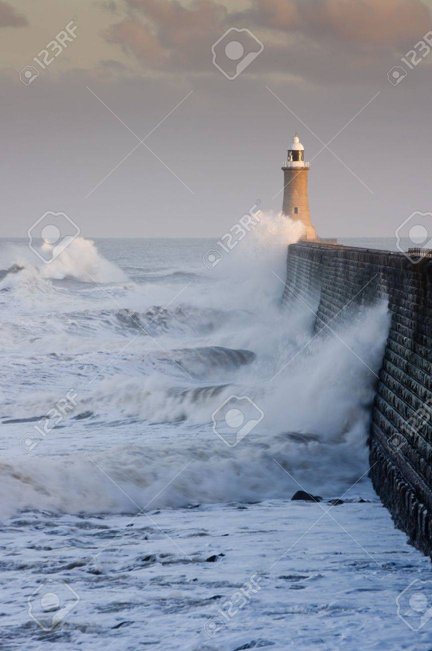 Tynemouth north pier with waves crashing against it and the lighthouse - 12693024