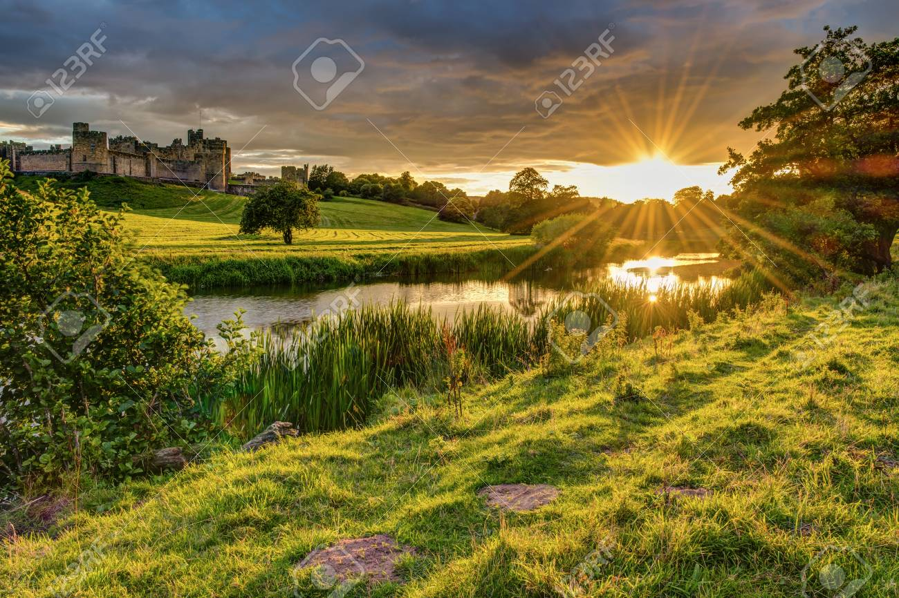 Sunbeams over River Aln at Alnwick, which runs through Northumberland from Alnham to Alnmouth. Seen here below Alnwick Town and Castle on the skyline, as the sun goes down - 84000358