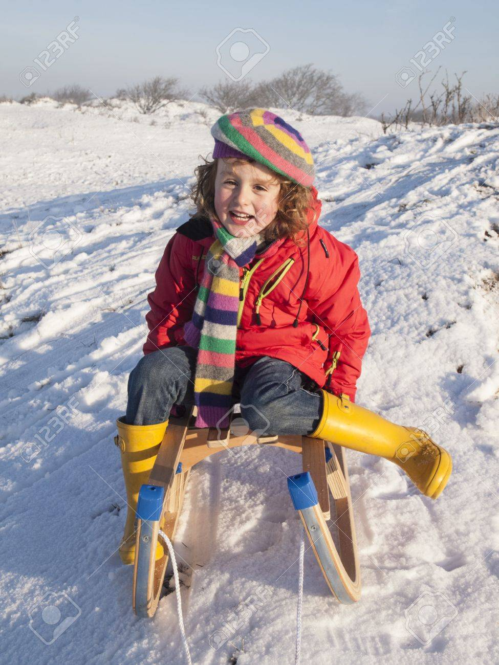 small girl in colourful winter clothing sat smiling on a wooden sledge  in a snow covered dune landscape Stock Photo - 17289044