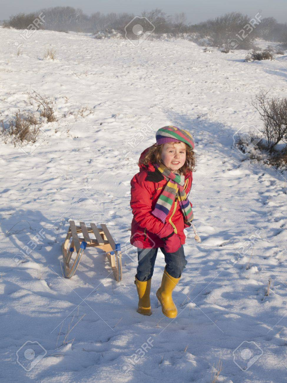 small girl in colourful winter clothing smiling while pulling a wooden sledge to the top of the hill in a snow covered dune landscape Stock Photo - 17289042