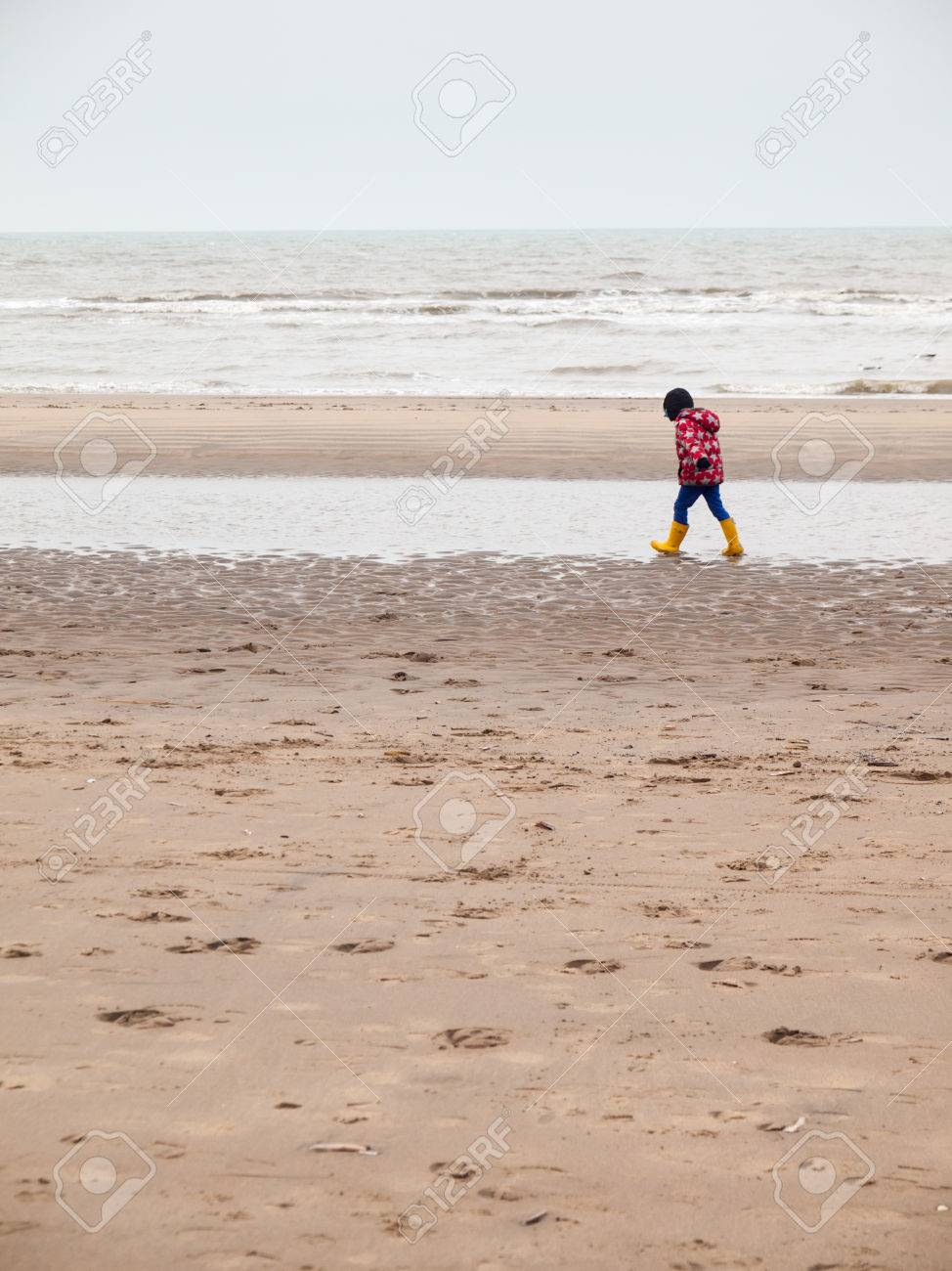 49792dbf2c small boy in winter clothing and rubber boots on a winter beach Stock Photo  - 26618858