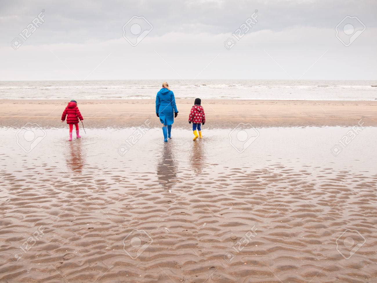a2bdb748c1 Stock Photo - woman with small boy and girl in winter clothing and rubber  boots on a winter beach looking out to sea