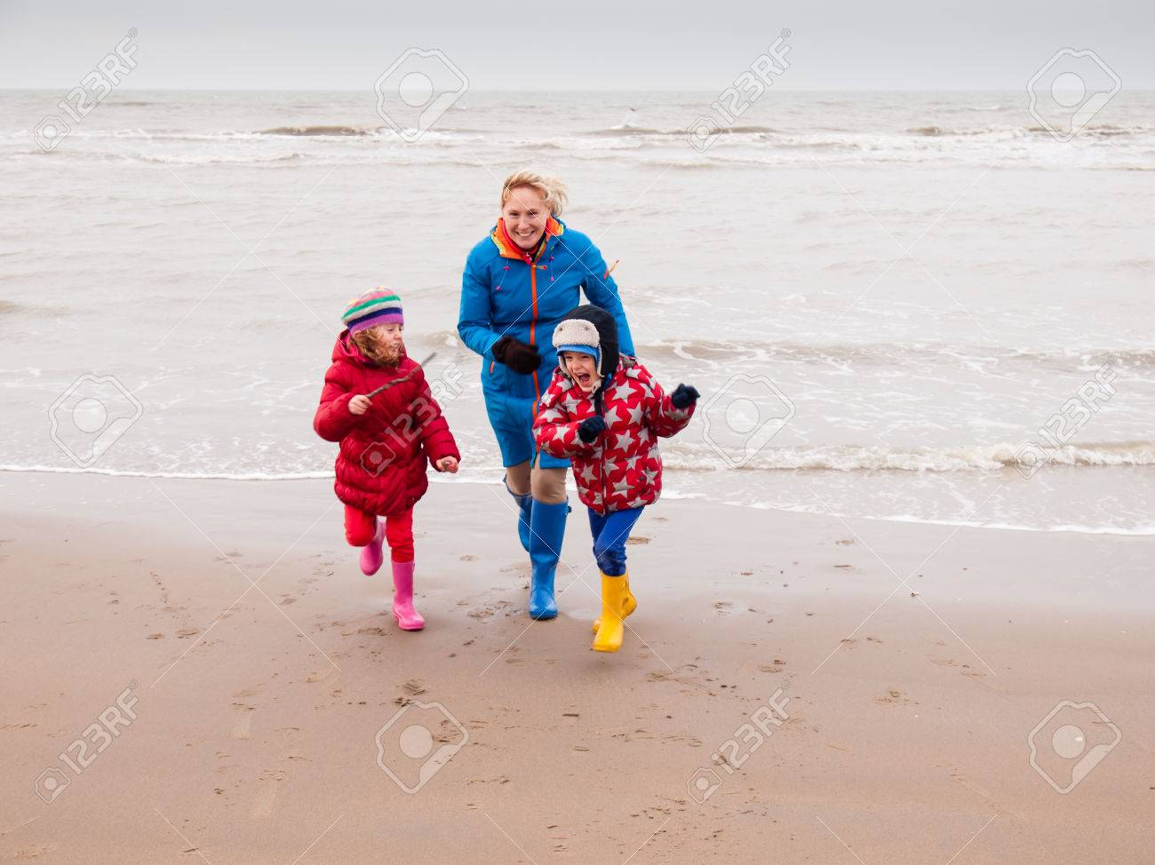 d46832b607 Stock Photo - woman with small boy and girl in winter clothing and rubber  boots playing on a winter beach running away from waves