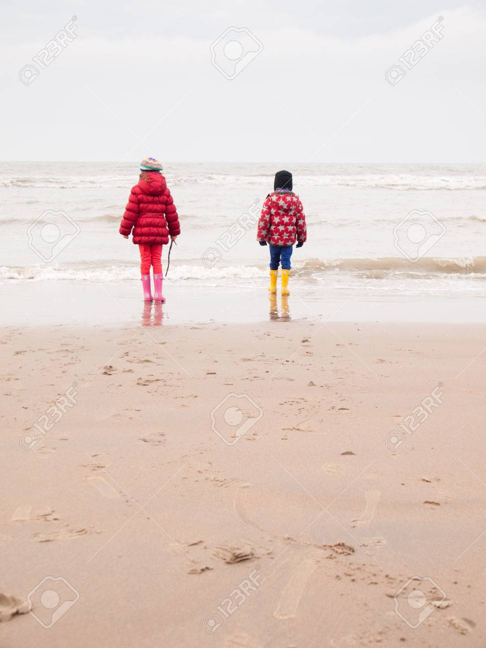 dfa708f781 small boy and girl in winter clothing and rubber boots on a winter beach  looking out