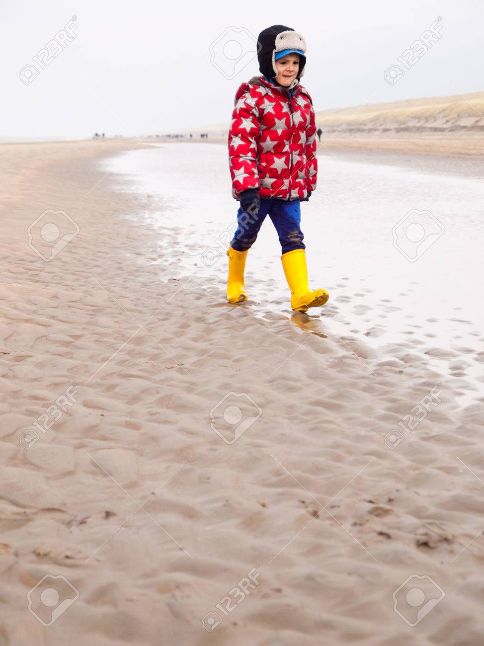 e5b8786c24 small boy in winter clothing and rubber boots walking on a winter beach  Stock Photo -