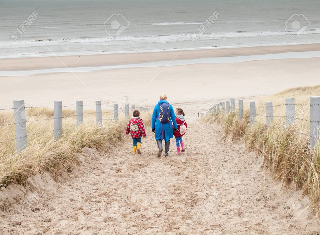 4fe9bd10ad Stock Photo - woman with small boy and girl in winter clothing and rubber  boots walking down to a winter beach along a dune path