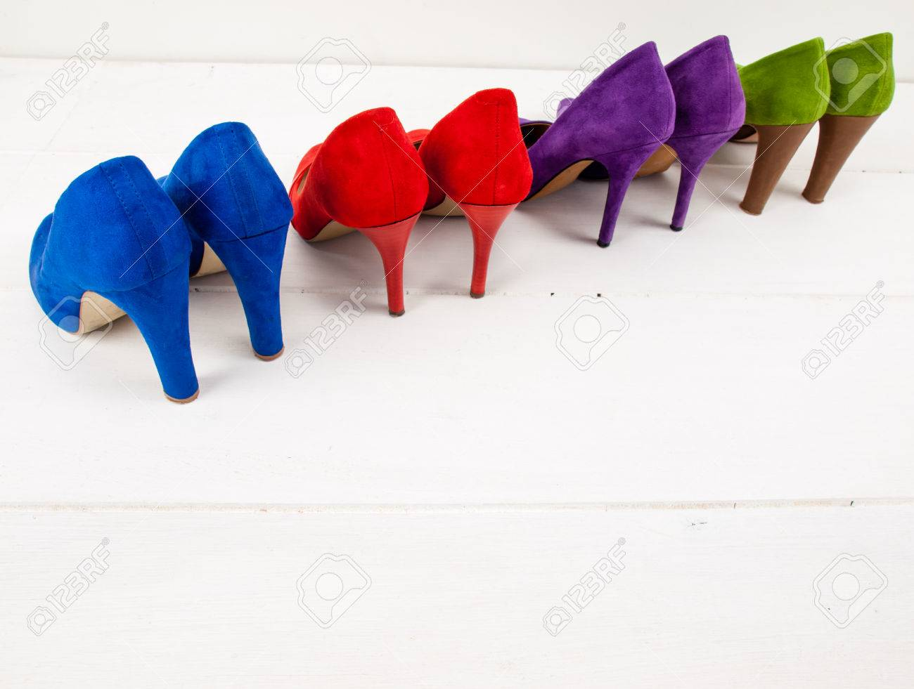 c3d5379ef2 four pairs colourful suede stiletto shoes lined up on the diagonal on a  white floor infront