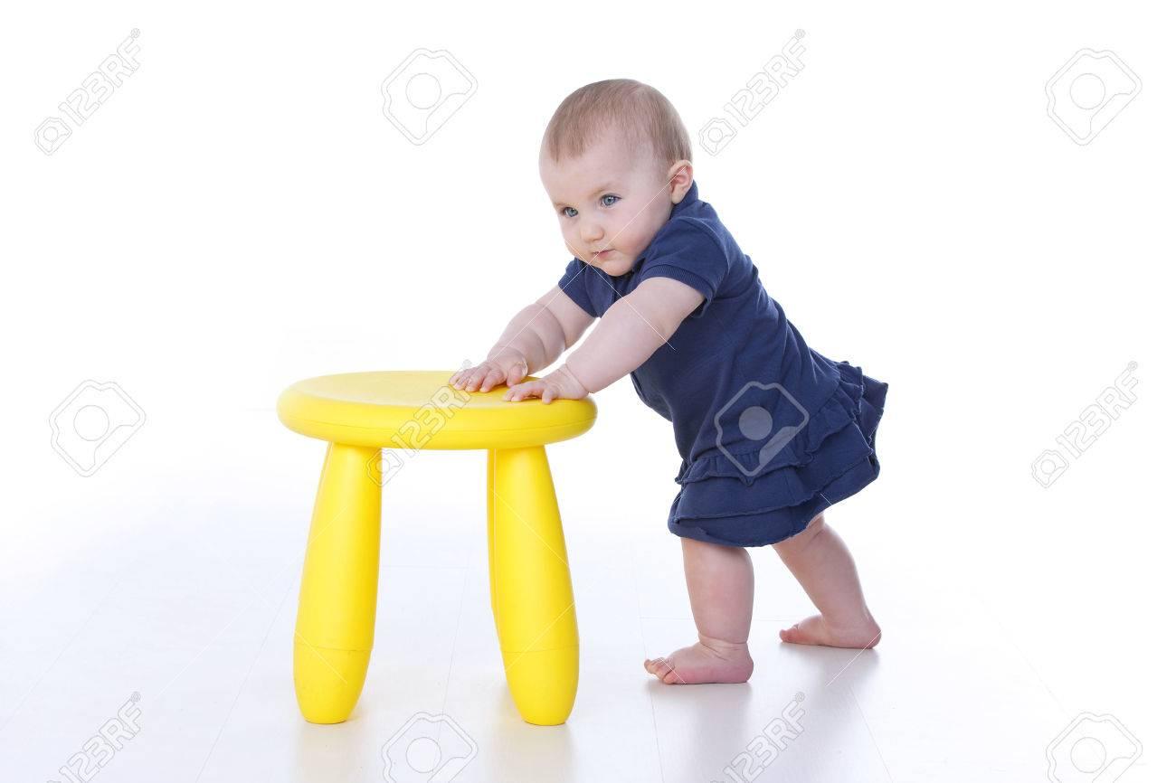 Baby Mädchen Drückt Stark Einem Gelben Stuhl Lizenzfreie Fotos