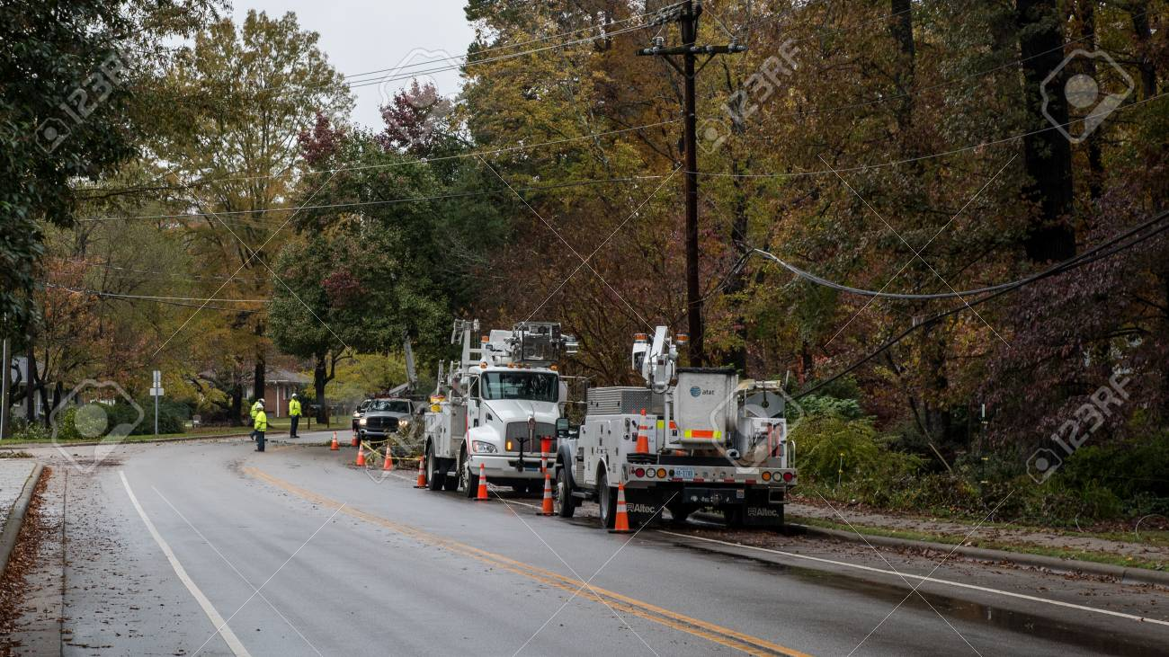 Carrboro, North Carolina, US-November 13, 2018: Workers repairing power lines after tree fell on them in storm - 112705442