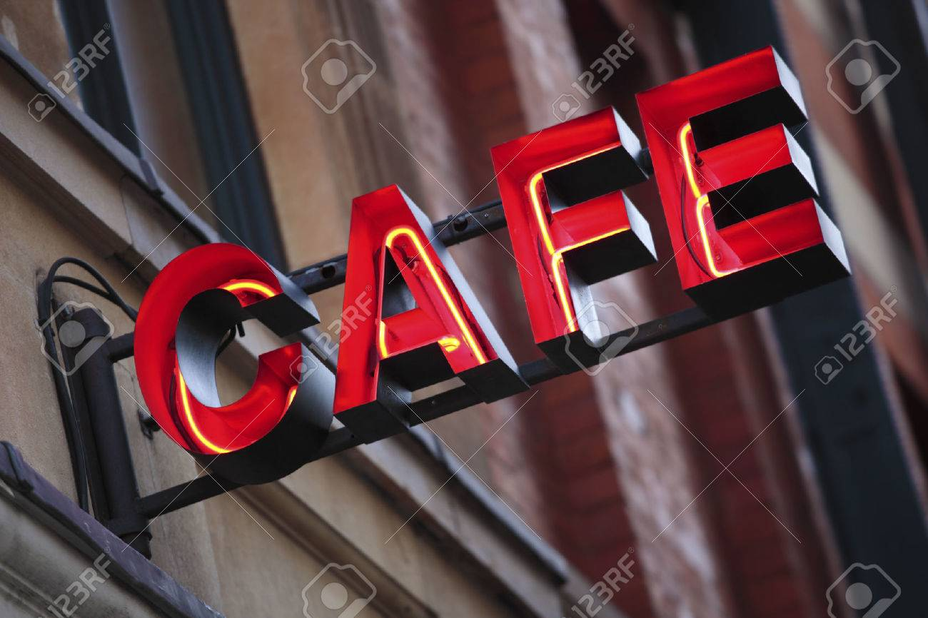 Neon cafe sign with out of focus building in the background. - 42541039