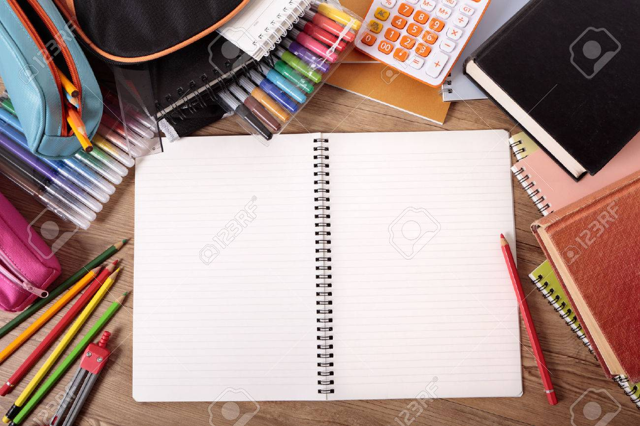 Busy student's desk with open notebook, school bag, text books and various pencils and crayons. - 43166754