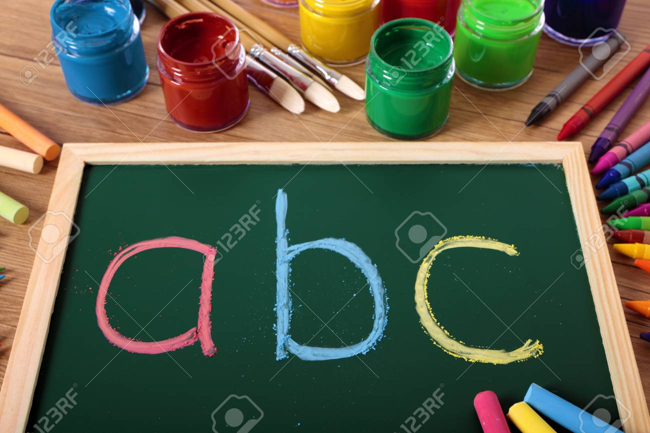 abc written in color chalk on a small elementary blackboard with