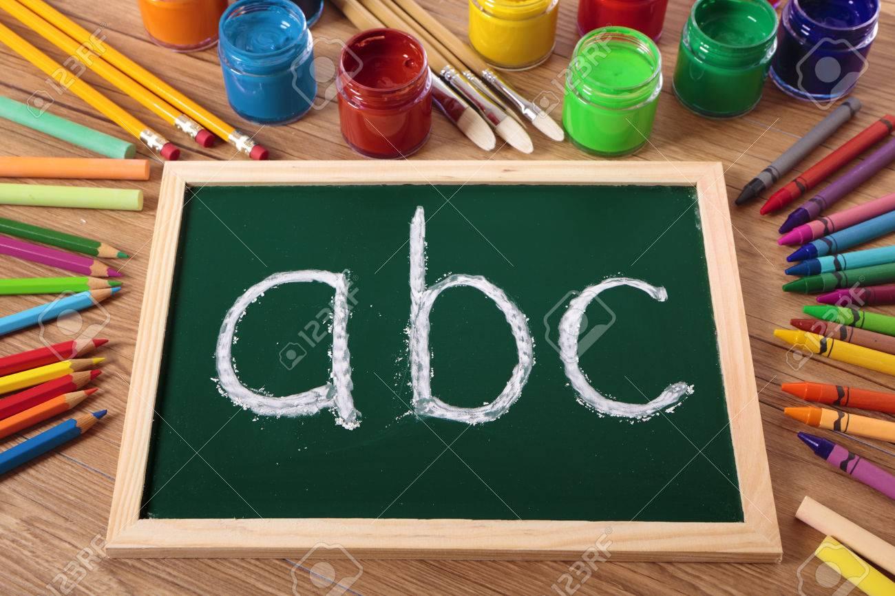 abc escrito con tiza en una pequea pizarra primaria con varias pinturas lpices de colores