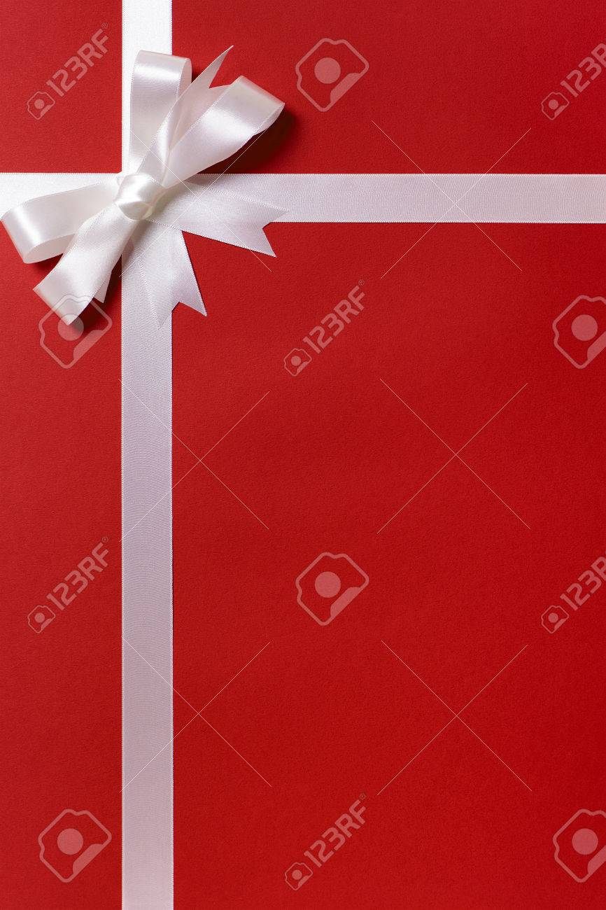 white ribbon bow red gift wrap paper background copy space