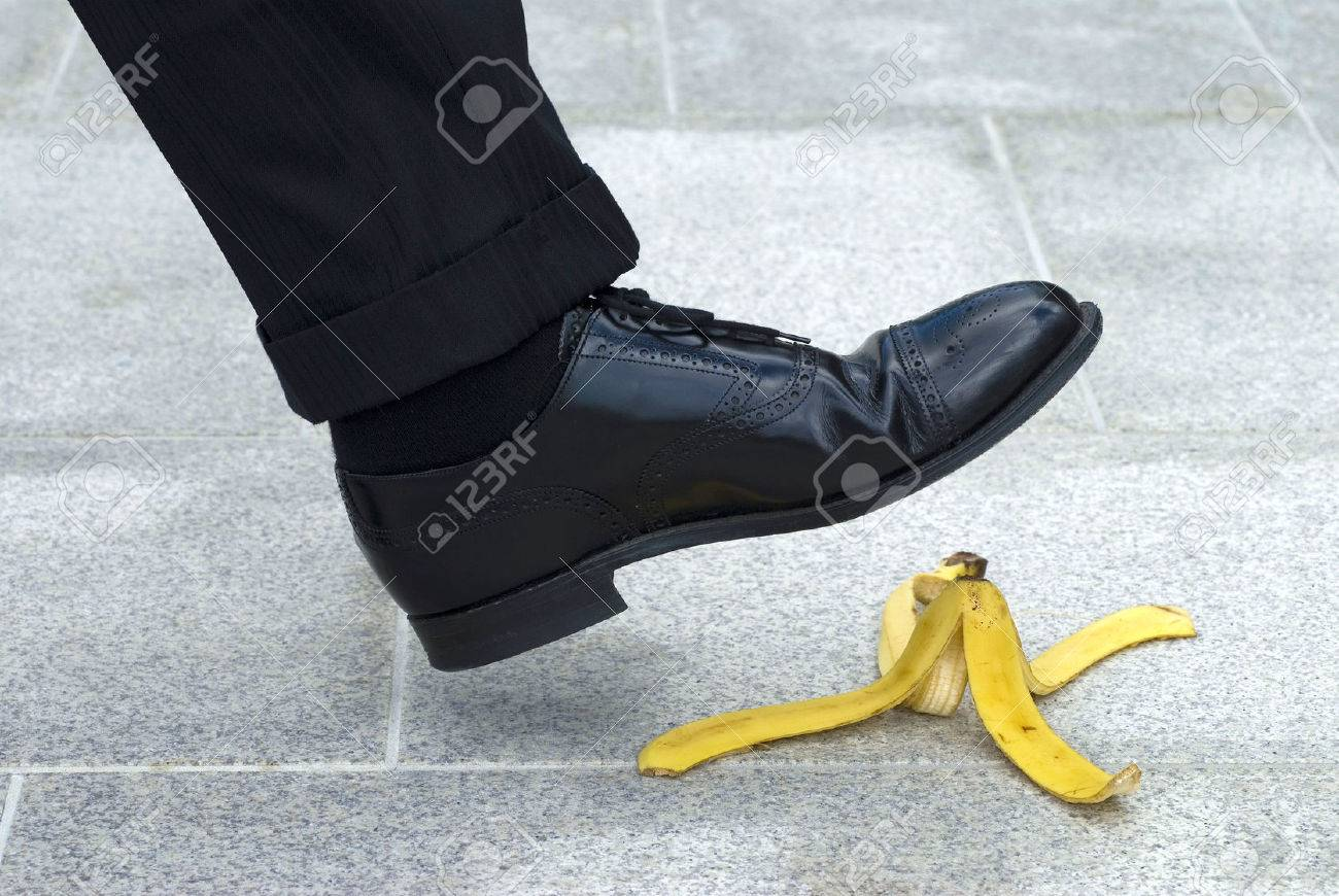 Businessman stepping on banana skin - 54148062