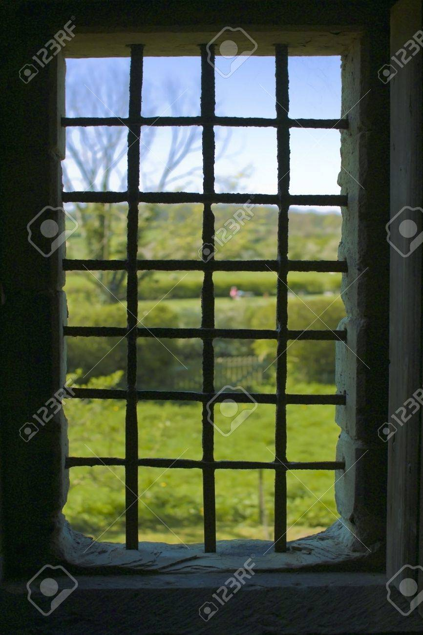 An old medieval window with bars in a castle looking at countryside outside. Stock Photo - 2302609