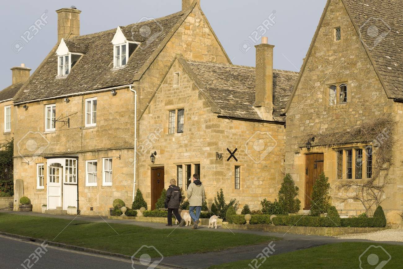 Town houses high street broadway cotswolds worcestershire uk, couple walking dogs. Stock Photo - 2538663