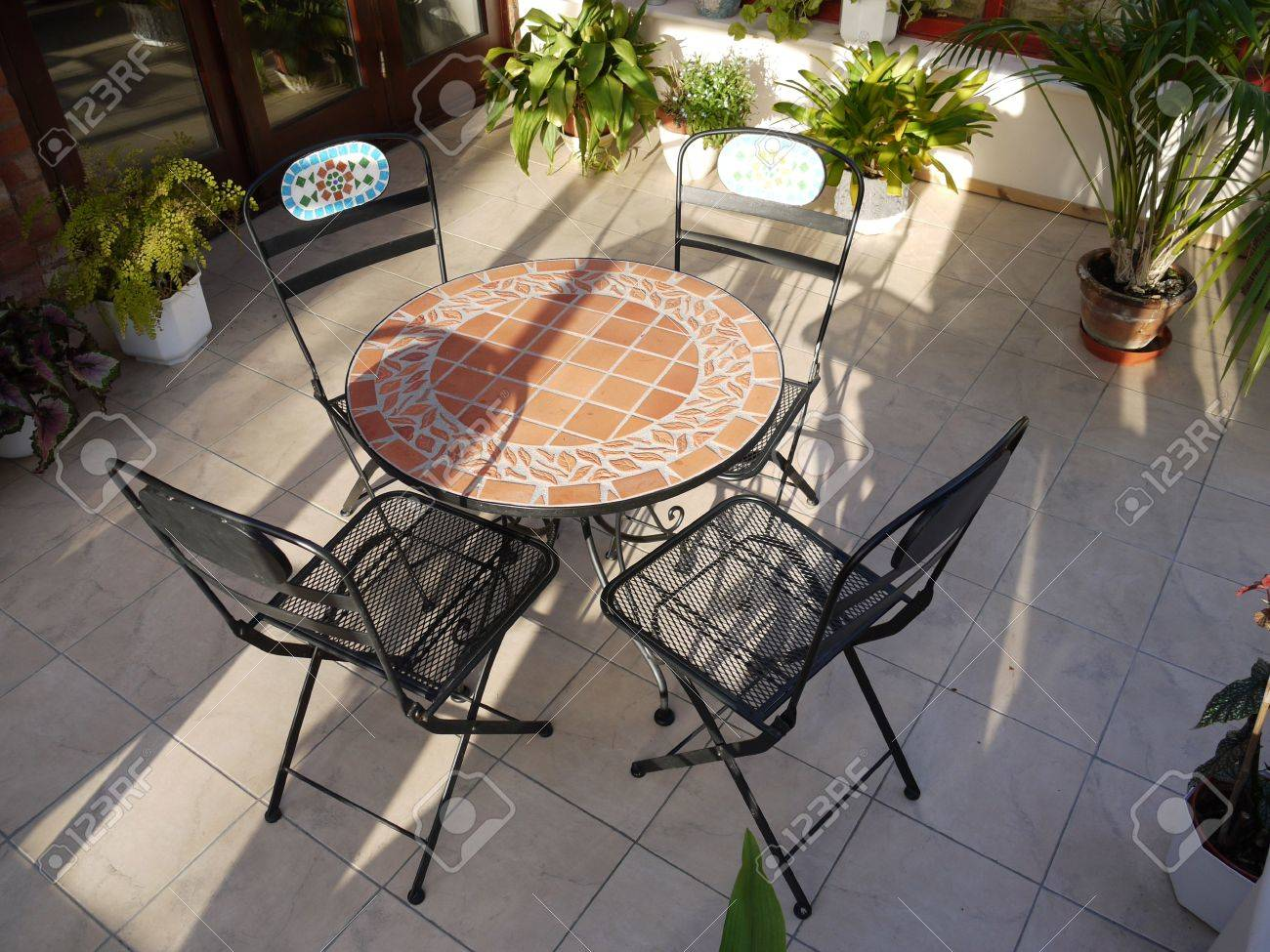 A conservatory with tables,chairs & plants in room in house next to garden. Stock Photo - 4781701