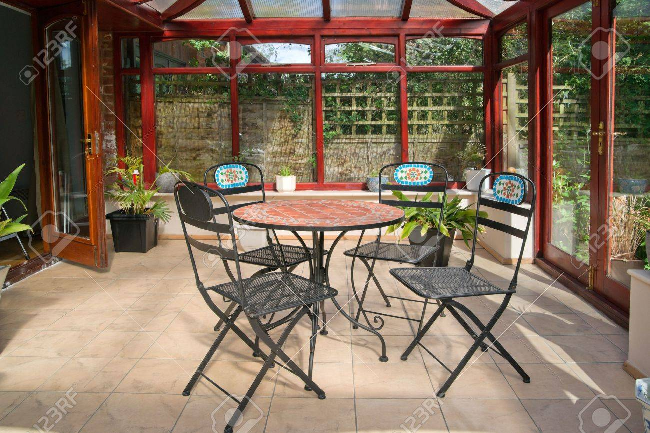 conservatory tables chairs plants room in house next to garden Stock Photo - 9627772