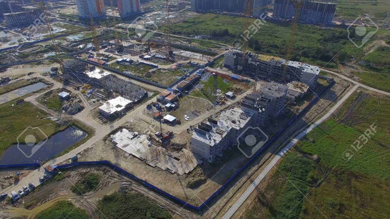 建設建物の空中写真。サイトの建設労働者、空中、トップ ビュー。大型クレーンで工事現場の俯瞰。建築現場や建築作業に折りたたまれた床の空撮。
