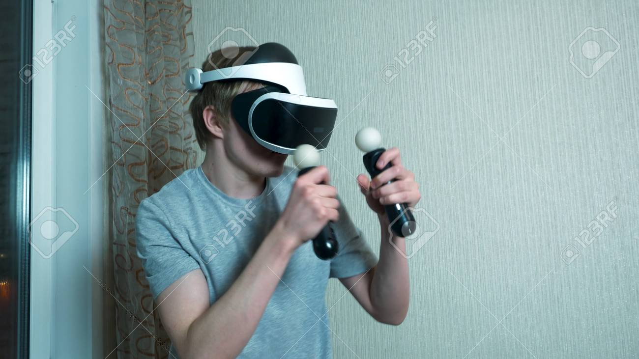 76478fb46356 Young man playing with virtual reality glasses and video game controller  isolated on a gray background. Man play on VR using joystick.