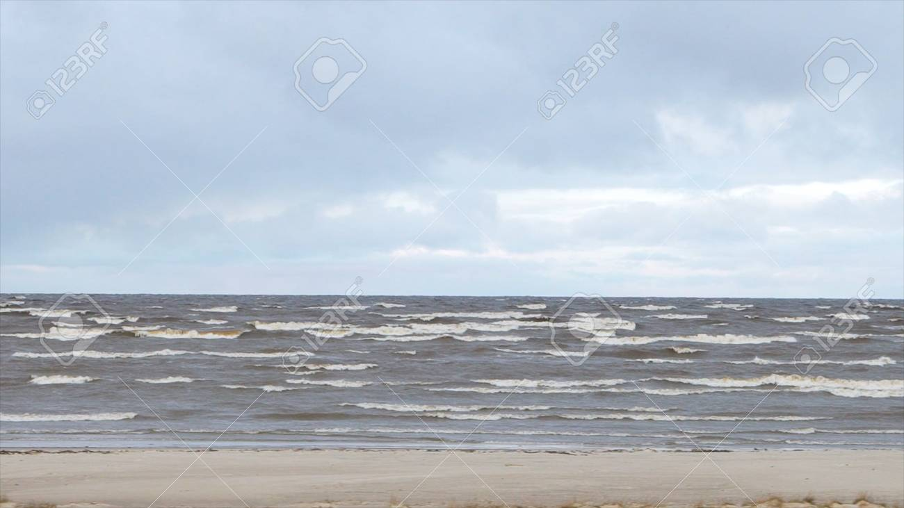 Sea coastal waves rolling on empty sandy beach, stormy cloudy