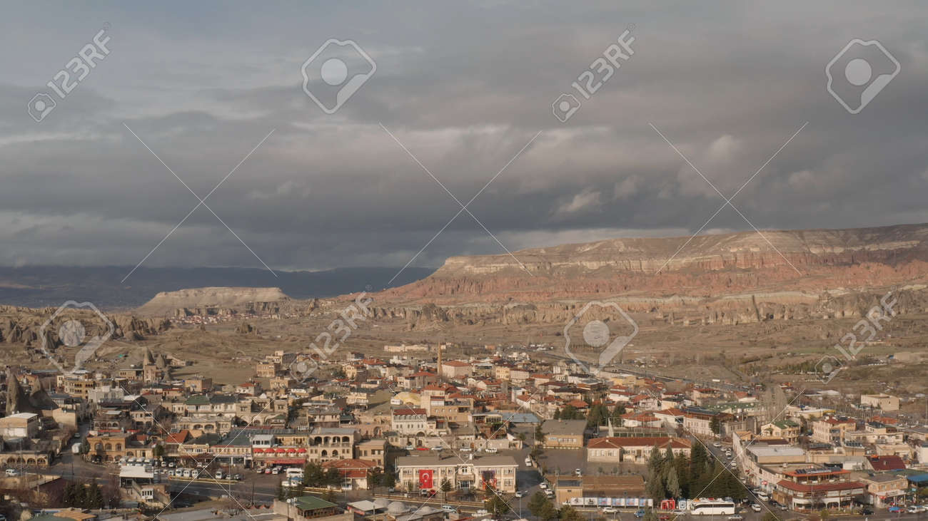 Aerial panoramic view of a southern city under bright hot sun on a summer day. Action. Many small houses and narrow streets on dry mountains on the background. - 169163190