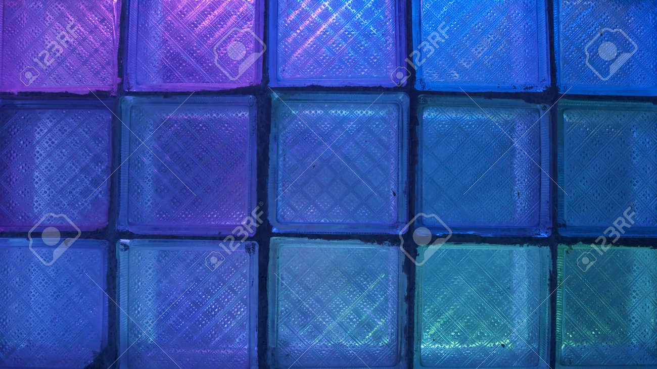 Square glass with neon light. Stock footage. Glass wall on background of flashing colored lights. Neon lights blink behind glass wall in nightclub - 169162811
