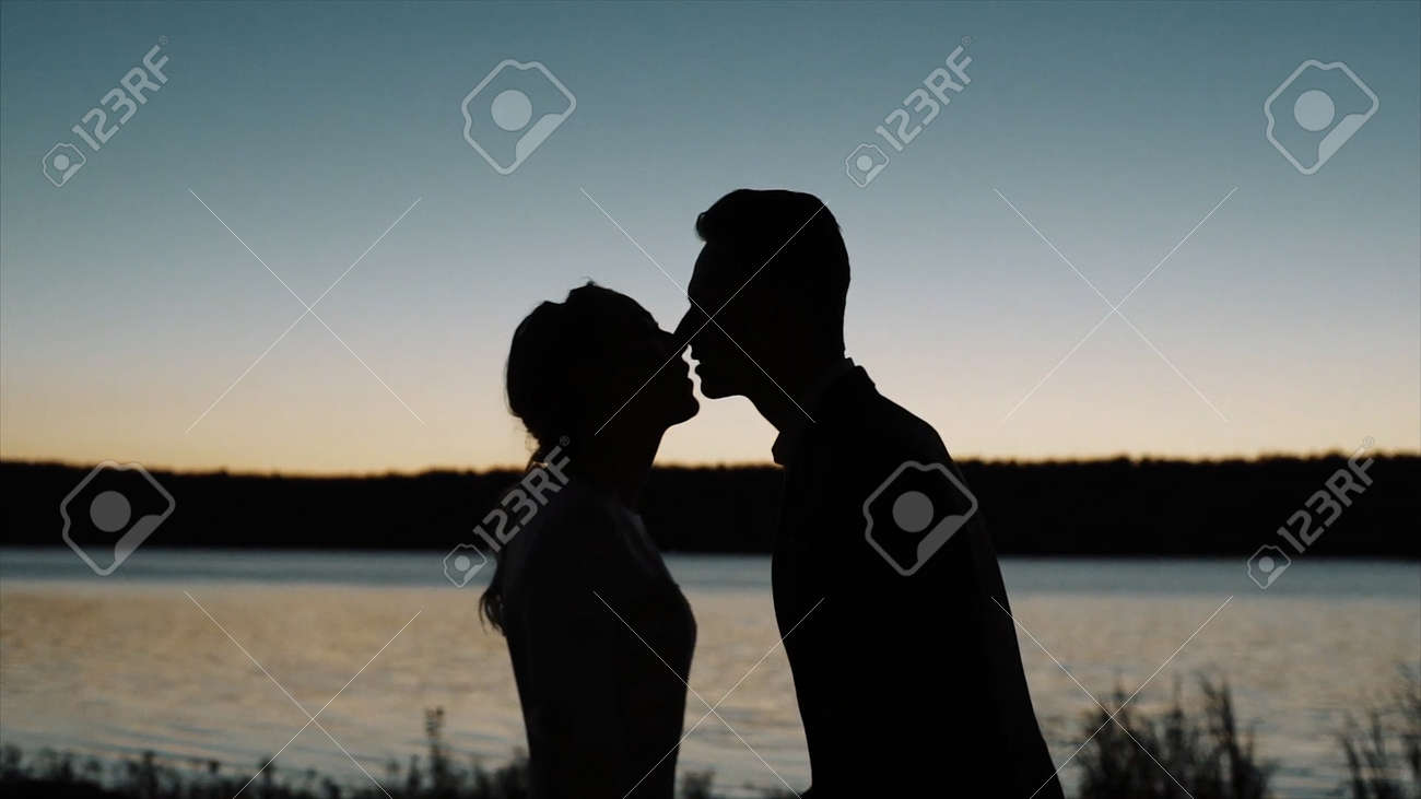 Silhouette of a couple in love at sunset in front of a river. Video. Side view of a man and a woman kissing during romantic date, concept of love. - 170180007