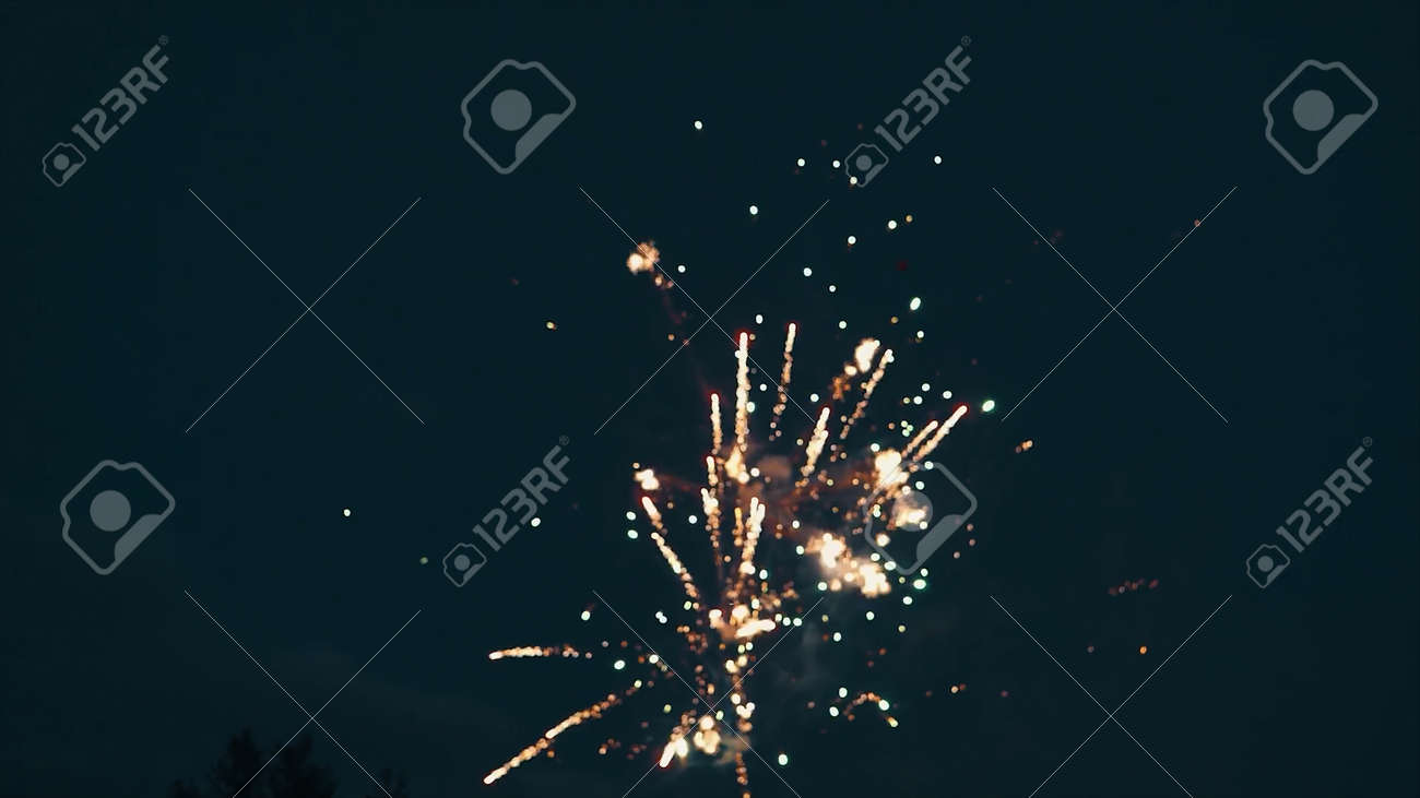 Bottom view of a dark blue night sky and exploding fireworks. Video. Blurred shining lights of fireworks, concept of celebration. - 170311837