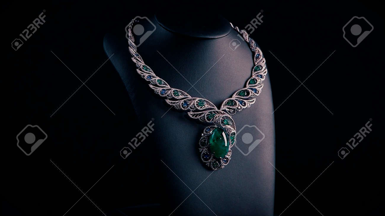 Beautiful necklace with blue sapphires and green emeralds on a black mannequin. Video. Close up of an expensive pendant of white gold and gemstones. - 170380538