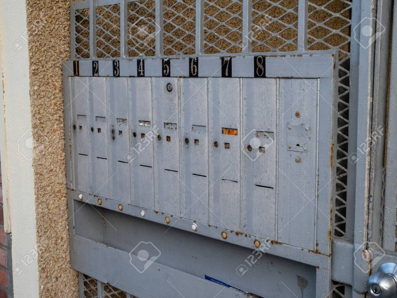 Outdoor apartment mailboxes with rusty look and dirty state units..