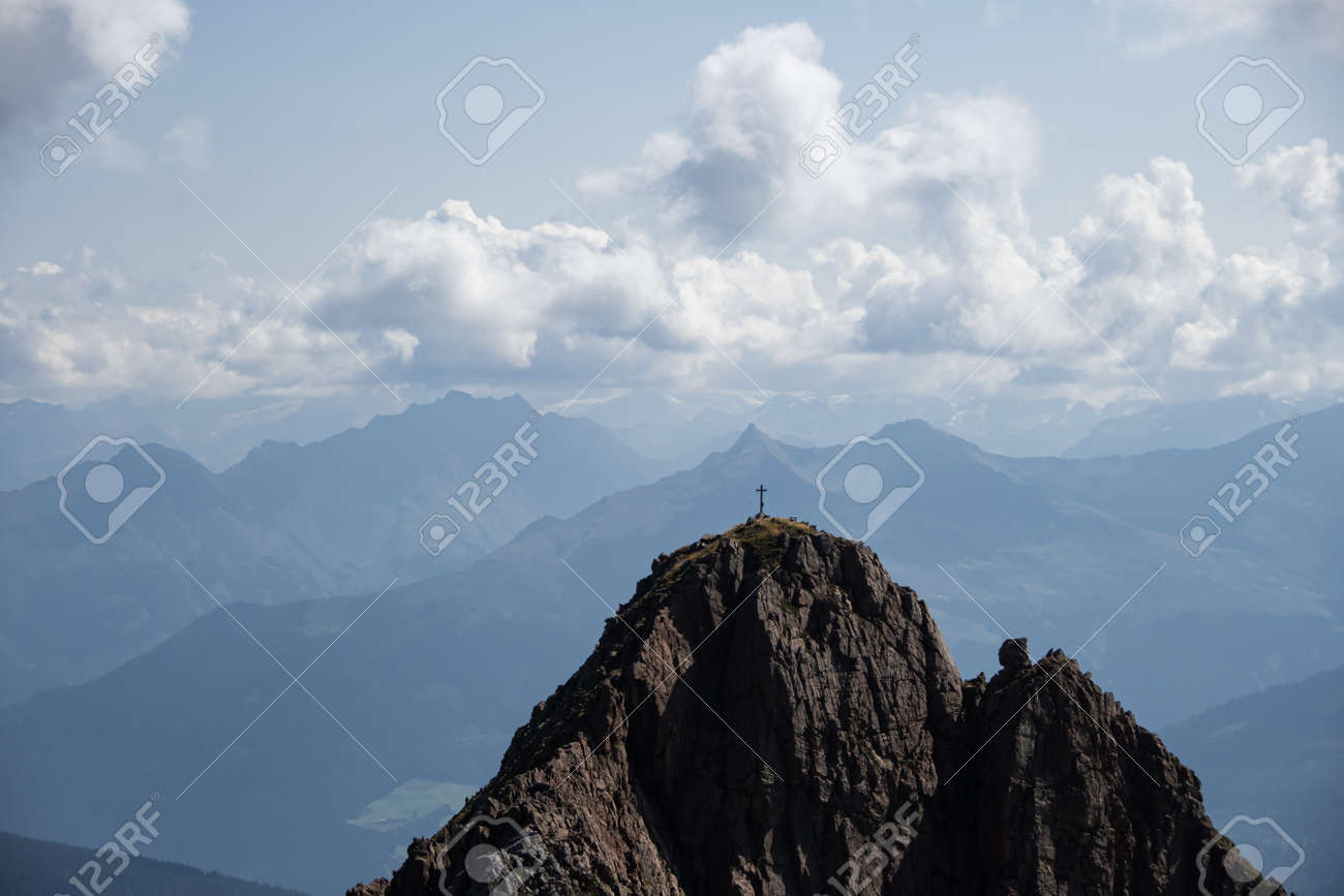 The summit of a high mountain with a summit cross in the background a mountain panorama with clouds - 156283427