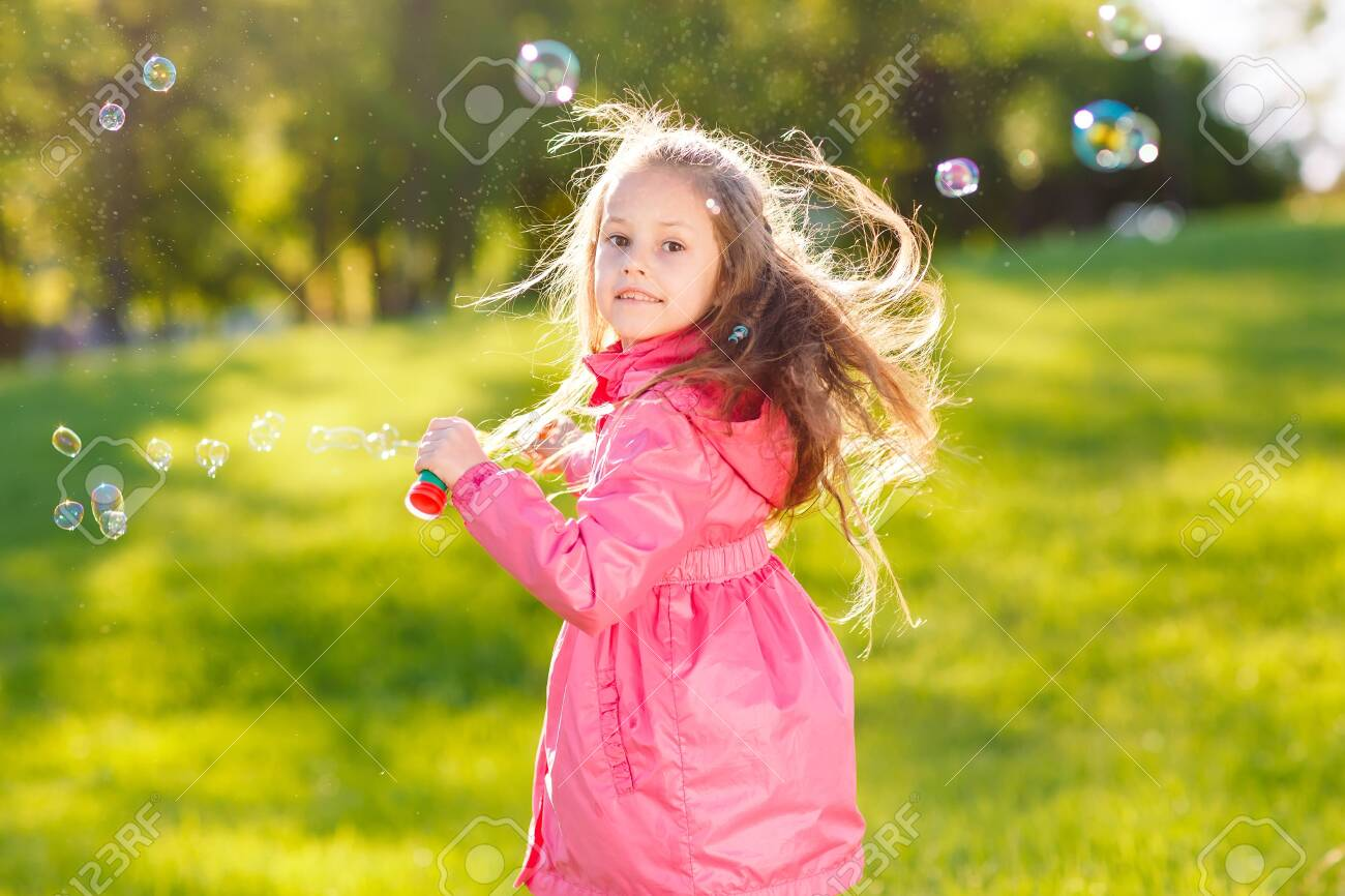 The girls run and play with soap bubbles. - 134556447