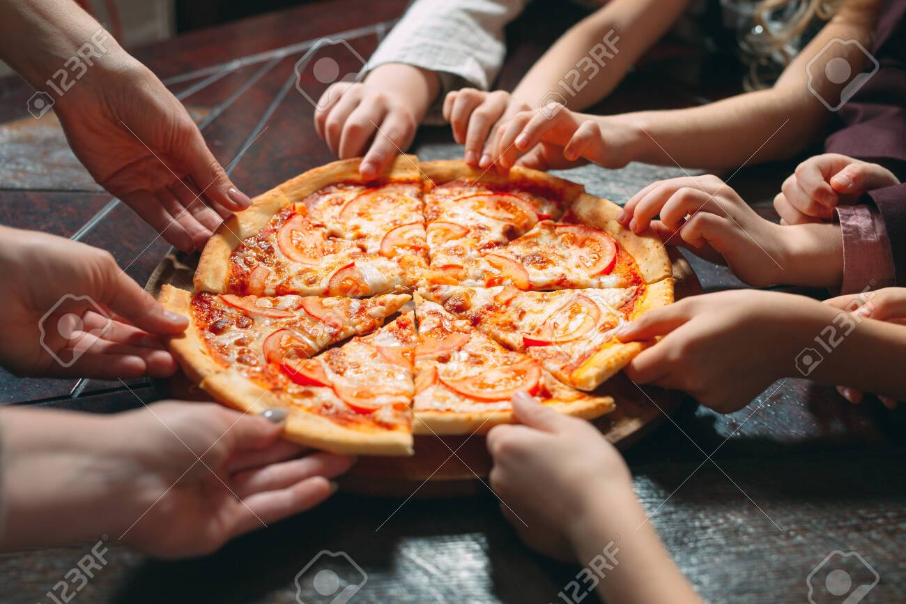 Hands taking pizza slices from wooden table, close up view - 128656960