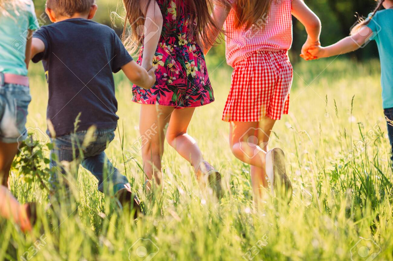 Large group of kids, friends boys and girls running in the park on sunny summer day in casual clothes . - 128593886