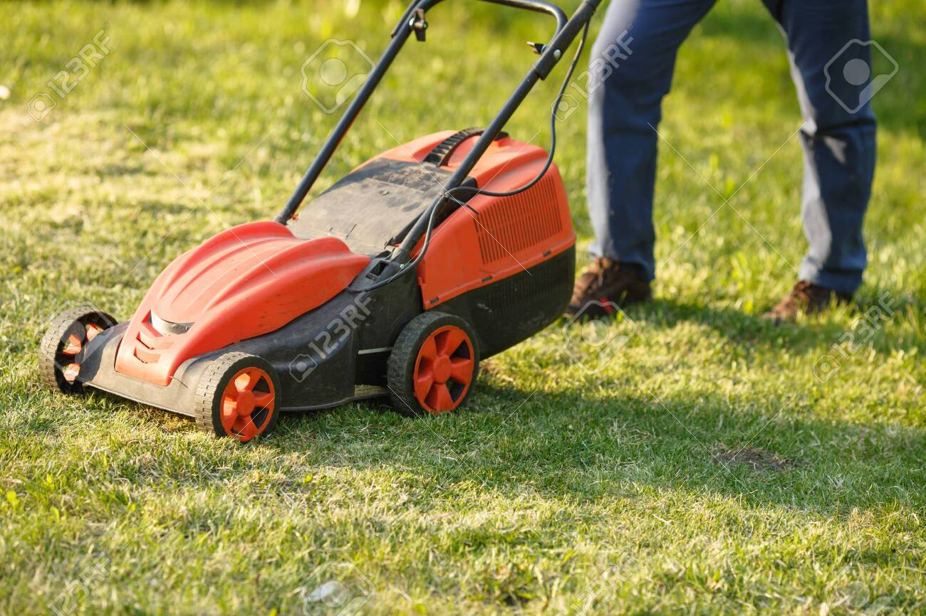 mowing trimmer - worker cutting grass in green yard at sunset. Man with electric lawnmower, lawn mowing. Gardener trimming a garden. - 153797691