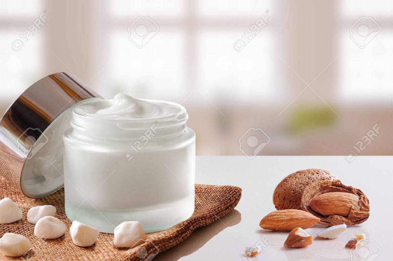 Glass open jar with facial or body almond moisturizer on burlap. With lid, small stones and almonds. Windows background. Front view. - 48201138