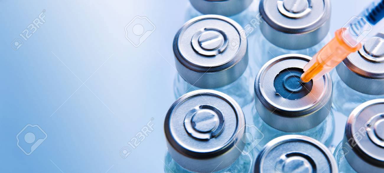 Group of vials with medication and punctured syringe on blue methacrylate table. Horizontal composition. Top view. - 88561061