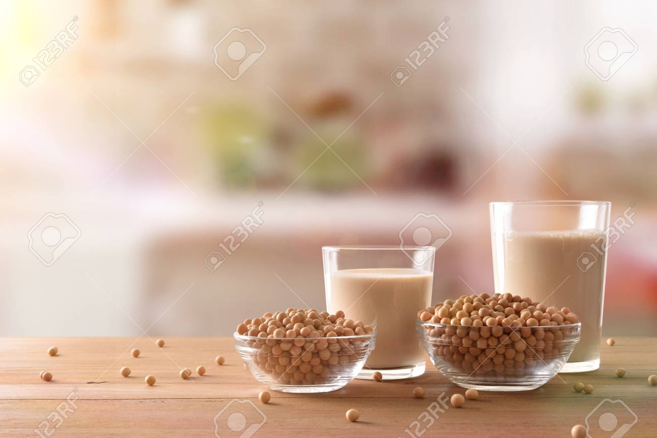 Reptientes with soy milk and grains on a wooden table and rustic kitchen background. Alternative milk concept. Front view. Horizontal composition - 99745675