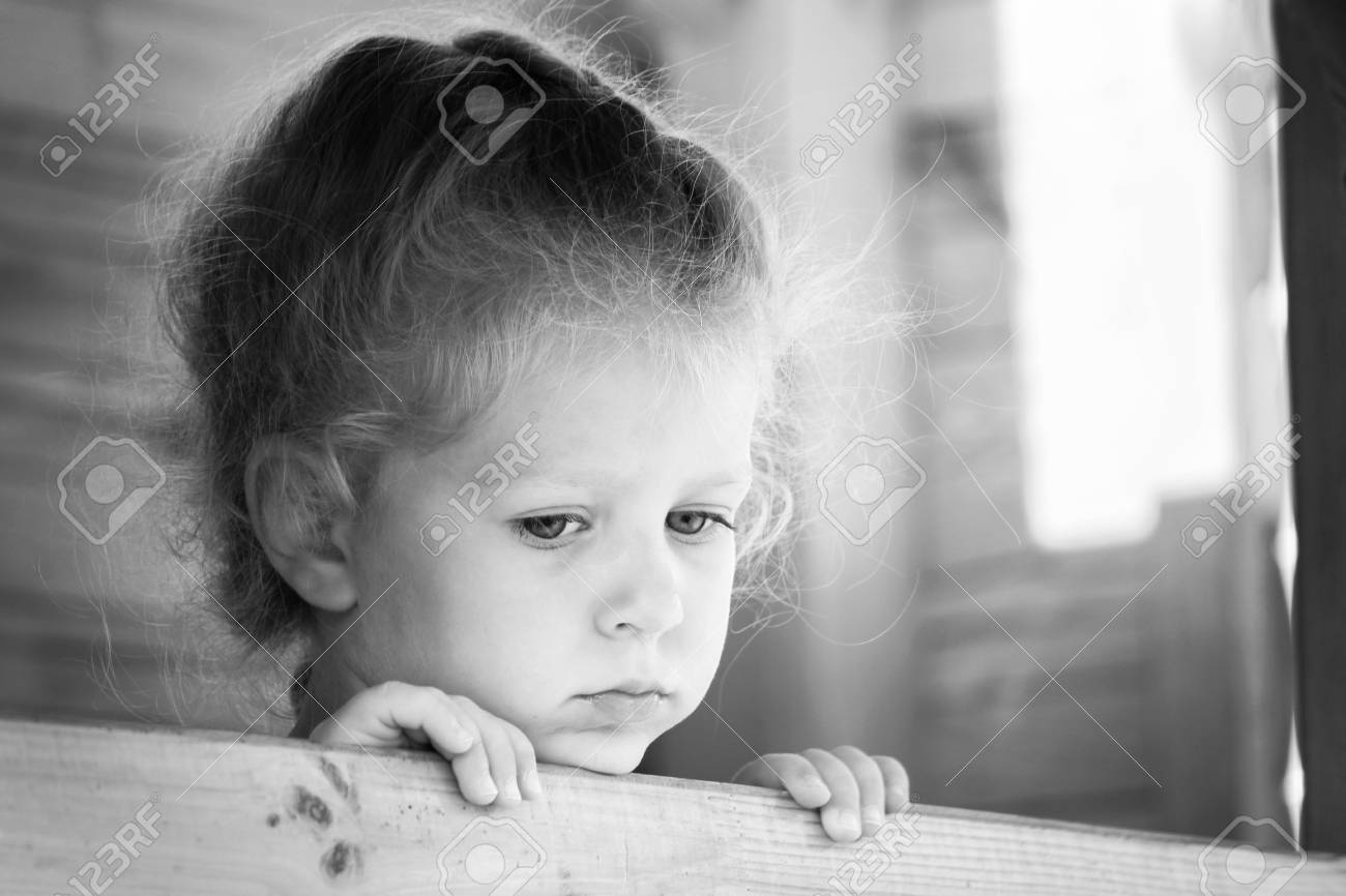 Little sad girl on the playground black and white series stock photo 85361073