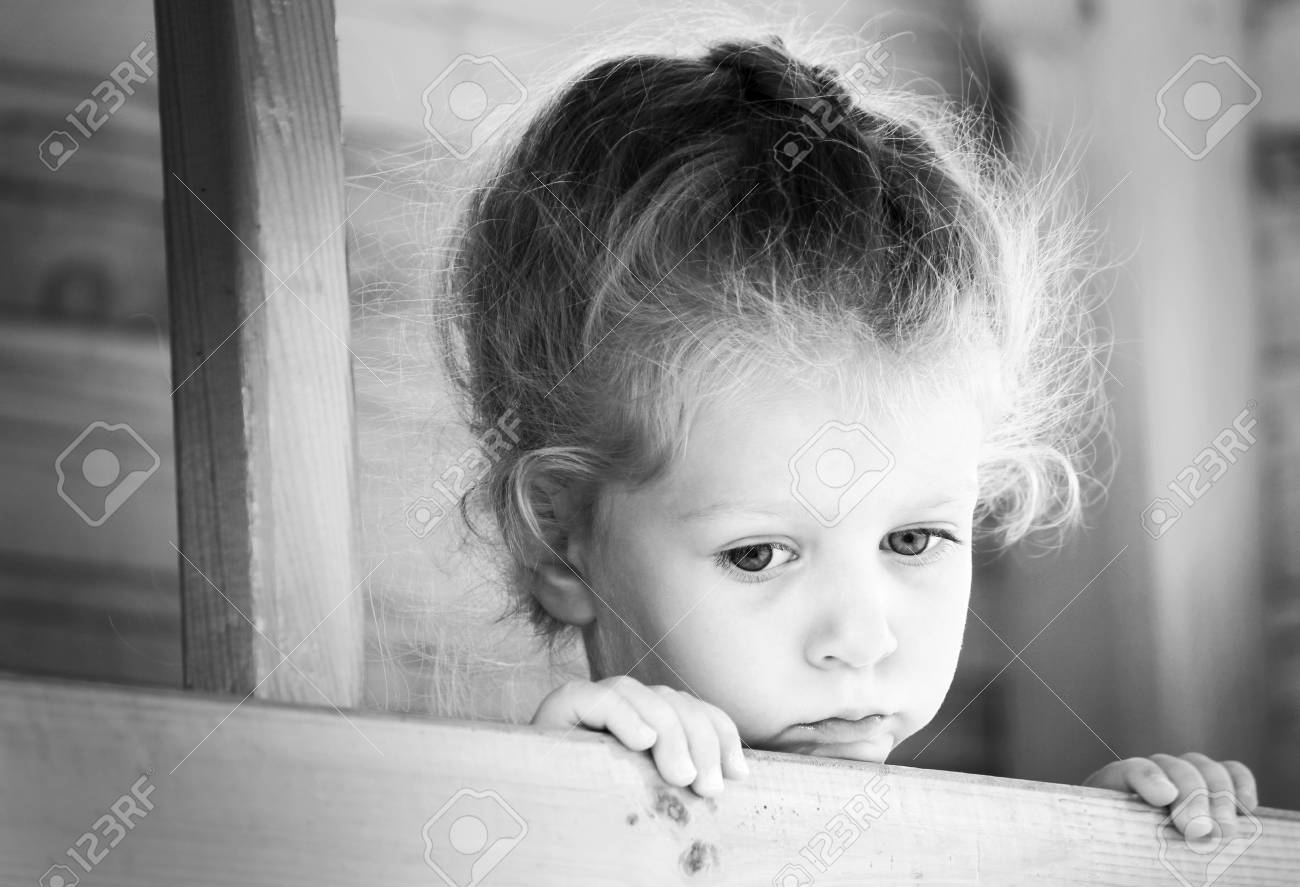 Little sad girl on the playground black and white series stock photo 85361087