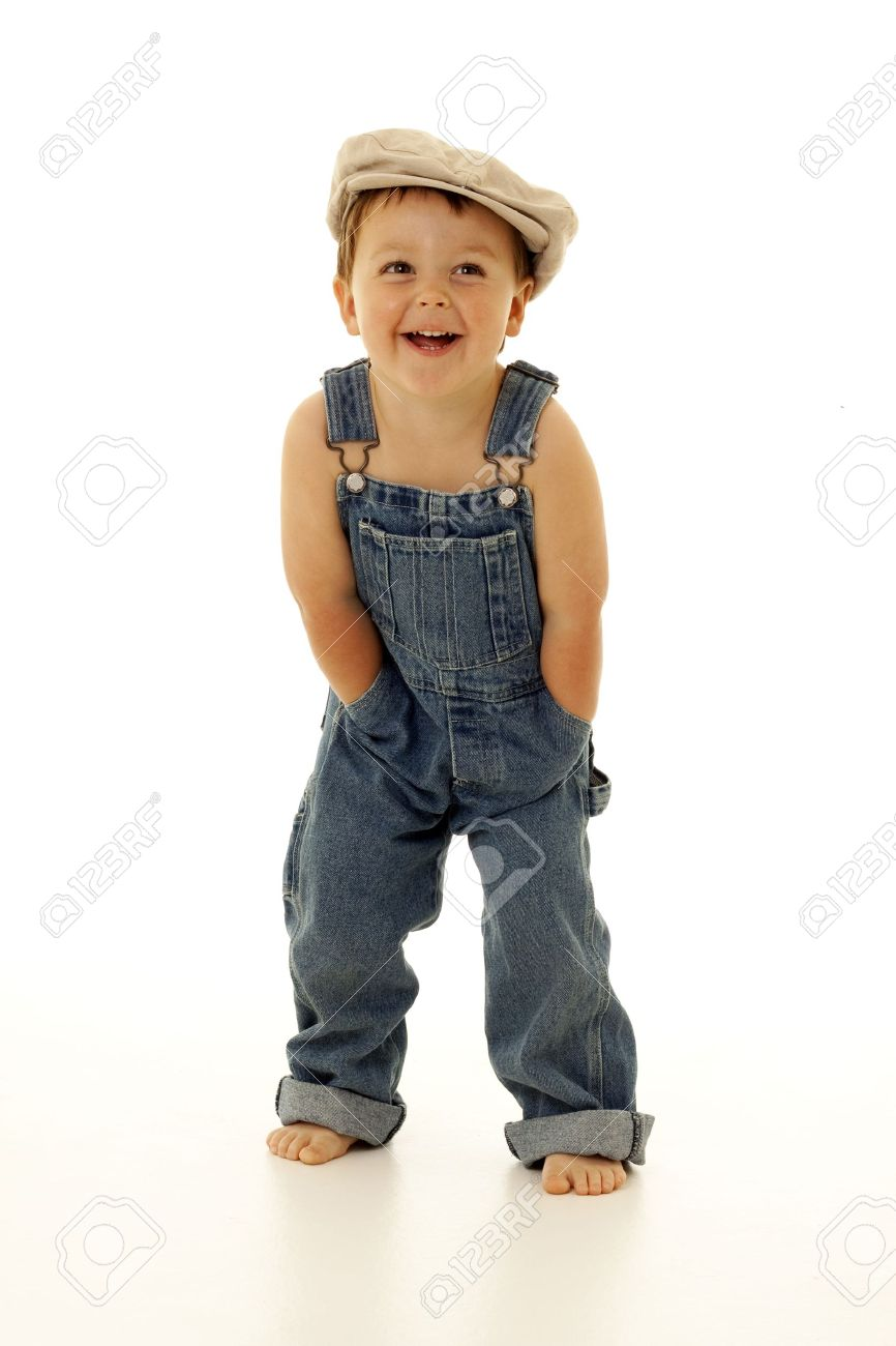Adorable Toddler In Overalls And A Vintage Hat Stock Photo