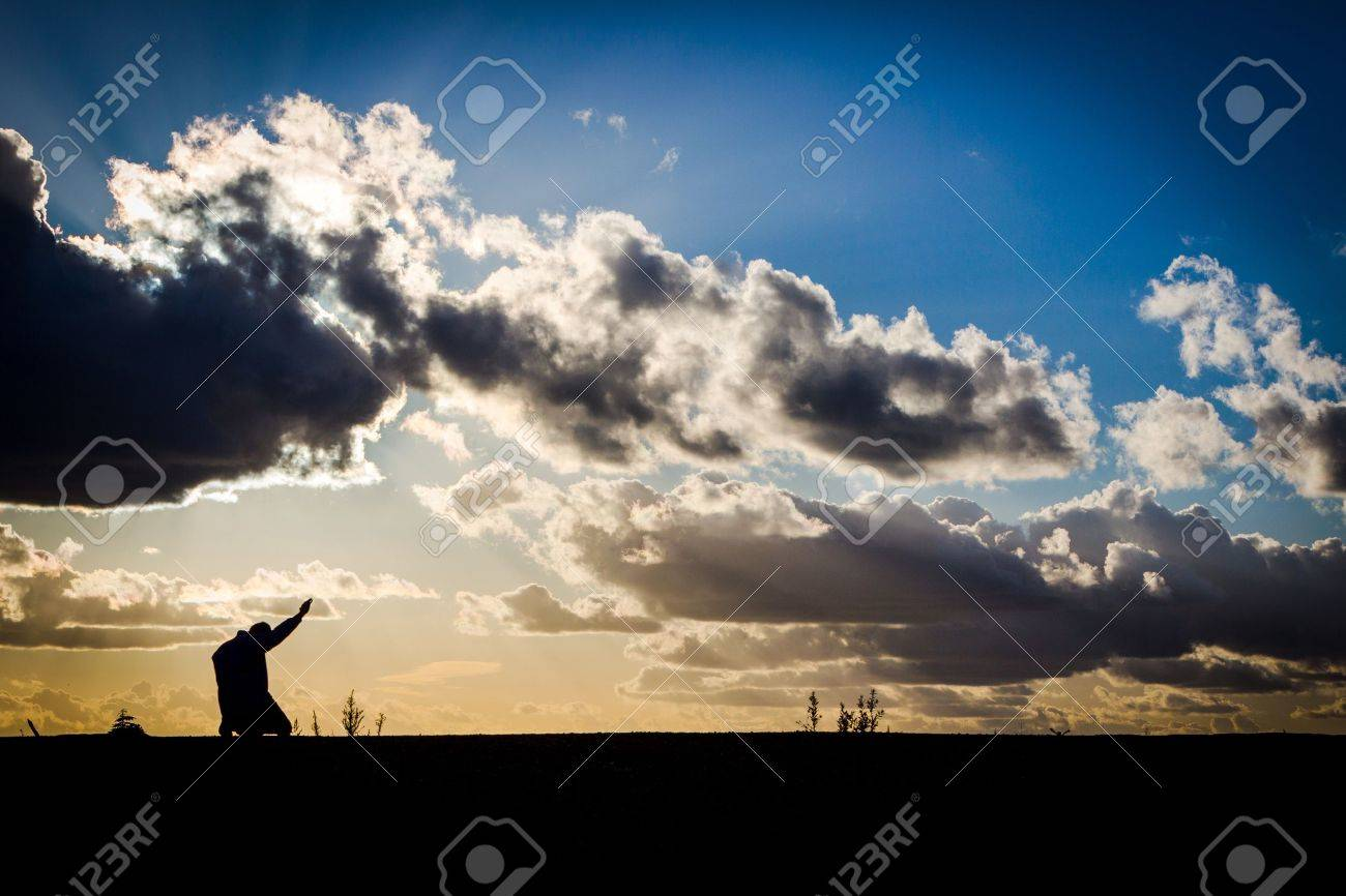 A man on his knees with arm raised in praise Stock Photo - 16250337