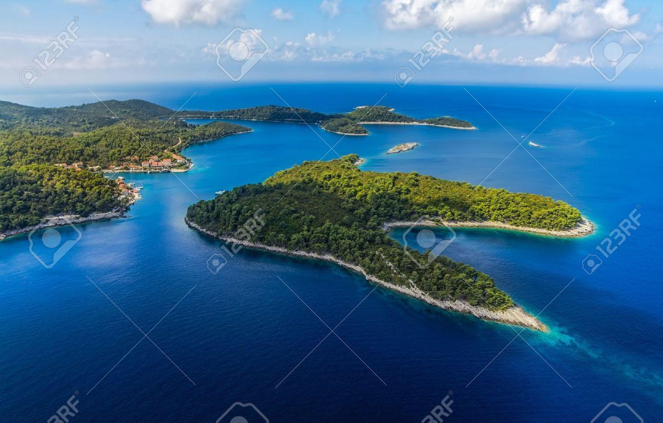 Aerial helicopter shoot of National park on island Mljet, village Pomena, Dubrovnik archipelago, Croatia. The oldest pine forest in Europe preserved. - 18808398