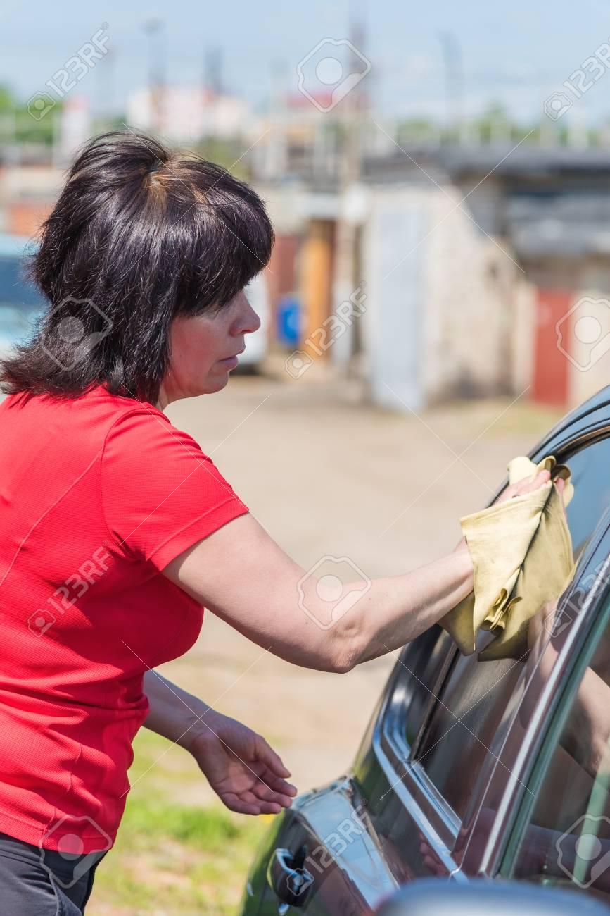 Brunette donna di mezza età in un maglione rosso lavare l'auto all'aperto